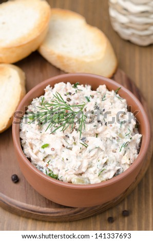 pate of smoked fish with sour cream, dill and toasted bread on a wooden board, top view