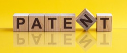 PATENT - word from wooden blocks with letters, concept, yellow background.