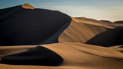 Path along stunning beige dunes outside in the desert with soft sunlight throwing shadows in the peaceful dusk.