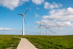path by the dike to the huge windmill park with huge turbines in the Netherlands Noordoostpolder, green energy wind mill park in Flevoland