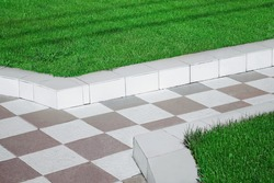 Path from Ceramic Tiles and Boarders Between Walkway and Backyard Lawn. Ceramic Tile Walkway. Garden Pathway from Black and White Tiles.