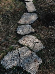 Path from pieces of asphalt laid out on grass