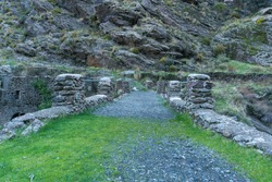 path in the Sierra Nevada mountain, there are several stone pillars with a metal railing,, there is a ruined construction, there are grass and bushes, there are rocks and stones