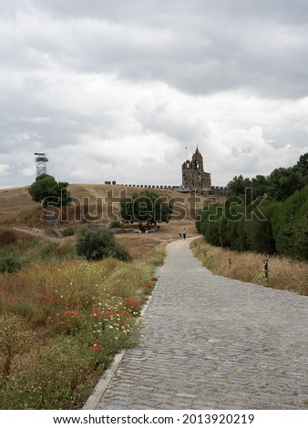 Path leading to the Clock tower in the Montemor-o-Novo Castle, flanked by trees and grass fields.  Montemor-o-Novo, Portugal. Foto stock ©