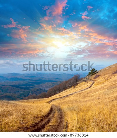 path on mountain meadow under sunset sky