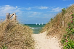 Path through dunes at the beach of the Baltic Sea with blue sky and clouds with sailboats in the Background near Heiligenhafen, Schleswig-Holstein, Germany. Summer landscape.