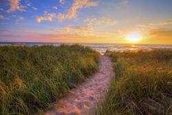 Path To A Sunset Beach. Winding trail through dune grass leads to a sunset beach on the coast of the inland sea of Lake Michigan. Hoffmaster State Park. Muskegon, Michigan.