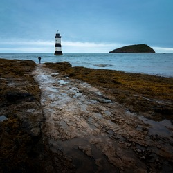 Path to the Penmon Point lighthouse in a cloudy day. Puffin Island in the background. Seaside landscape