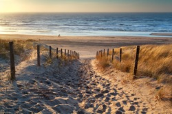 path to the sea and couple on beach at sunset, North sea, Holland