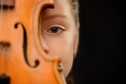 Pathetic glance. Close up of the eue of little girl holding the violin and hiding behind it