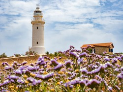 Pathos. Cyprus. White lighthouse on the background of the sky. Lighthouse on the Mediterranean Sea. Sights of the city of Pathos. Lighthouse in the archaeological park. Tours in Cyprus. Travels