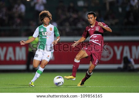 PATHUM THANI,THAILAND-APRIL 7:Paitoon Nontadee (red) in action during Thai Premier League between Bangkok Glass FC.and Insee Police UTD.at Leo Stadium on April 7,2012 in PathumThani,Thailand