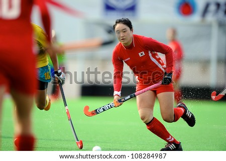 PATHUM THANI,THAILAND-JULY 3:Hong Jiseon (Red) of Korea runs with the ball during the Women�s Junior AsiaCup Korea and Kazakhstan at QueenSirikit Stadium on July3,2012 in PathumThani,Thailand.