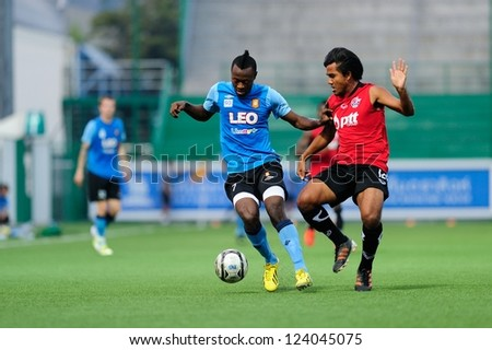 PATHUMTHANI,THAILAND-9 JANUARY 2013 : Christ Mbondi Players of Bangkok Glass FC(blue) in action during a friendly match between Bangkok GlassFC and PttrayongFC at Leo Stadium on JAN 9,2013 in Thailand