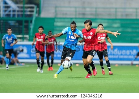 PATHUMTHANI,THAILAND-9 JANUARY 2013 : Christ Mbondi Players of Bangkok Glass FC(blue) in action during a friendly match between Bangkok GlassFC and PttrayongFC  at LeoStadium on JAN 9,2013 in Thailand