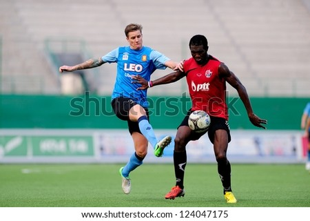 PATHUMTHANI,THAILAND-9 JANUARY 2013 : Players of Bangkok Glass FC(blue) in action during a friendly match between Bangkok Glass FC and PttrayongFC  at Leo Stadium on JAN 9,2012 in Thailand