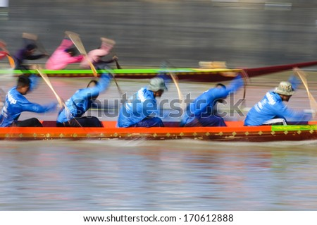 PATHUMTHANI, THAILAND - NOV 03: Panning shot of two rowing teams in full speed during Thai Long-tailed Boat Competition along river on November 03, 2013 in Samkhok, Pathumthani, Thailand.