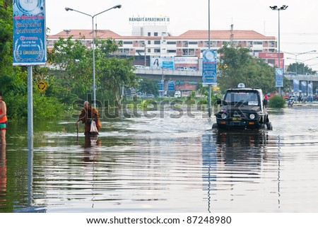 PATHUMTHANI, THAILAND - OCTOBER 18 -Thai flood hits Central of Thailand, higher water levels expected, car and peoples navigating through the flood- Tuesday october 18, 2011 in Pathumthani, Thailand