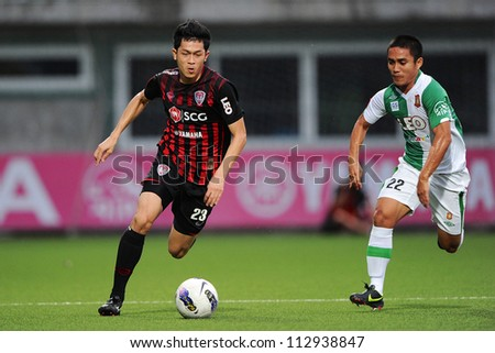PATHUMTHANI,THAILAND-2 SEPTEMBER: Piyaphon Bantao (red) of SCG Muangthong Utd in action during Thai Premier League between Bangkok Glass.and SCG Muangthong Utd.at Leo Stadium on Sep 2,2012 in Thailand