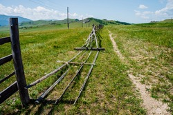Pathway along broken wood fence and poles with wires in mountains in sunny day. Beautiful sunny alpine landscape with footpath along field behind long fence in highlands. Vivid mountain scenery.