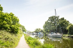 pathway along the canal of chelmer and blackwater navigation with boats on the water