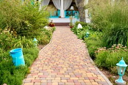 Pathway from colored concrete paving slabs stone between fresh green  grass in garden, copy space. Garden walk way. Pathway with blooming flowers. Gardening concept