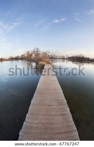 pathway, journey or goal concept - boardwalk and trail across lake and swamp, wide angle fish eye lens perspective, late fall scenery with ice cover