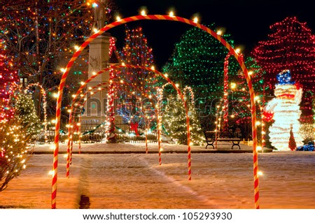 Pathway of candy cane arches leading to a brightly lit village Christmas display