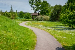 Pathway s curve in public park during sunny day, nobody. The way in the park with place for exercise and relax.