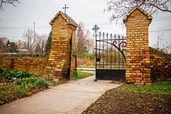 Pathway to arched gate in old brick wall with holy decorations