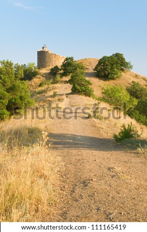 Pathway to ruins of a watch tower between dry grass and green trees