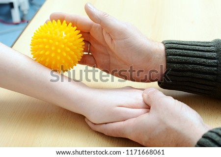 Patient at occupational therapy works with hedgehog ball to stimulate motor skills #1171668061