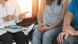 Patient couple having doctor or psychologist consulting on marriage counseling, family medical healthcare therapy, fertility treatment for infertility, or psychotherapy session concept