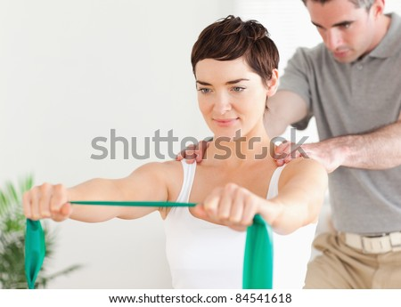 Patient doing some special exercises under supervision in a room - stock photo