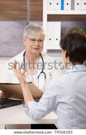 Patient gesturing to smiling doctor in bright office.?