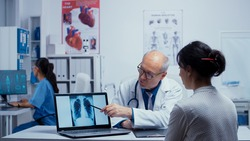 Patient having clean lungs at doctor appointment, discussing results with medic. Elderly senior experienced doctor talking with patient about lungs, x ray pneumonia, cancer, examination specialist