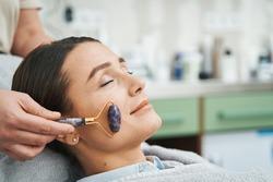 Patient having her cheek massaged with an amethyst roller