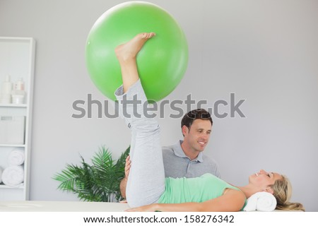 Patient holding exercise ball between legs in bright office