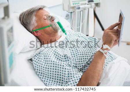 Patient is lying in bed reading wearing an oxygen mask in hospital ward