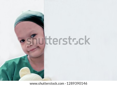 Patient kid lean against the wall in patient suit with her doll.Girl cover her head with headscarf.Kid look tired and sick but she still smiling. Concept of   childhood cancer awareness or encourage