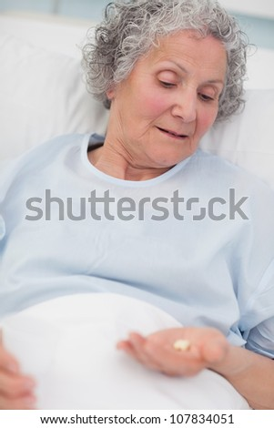 Patient looking at drugs in her hand in hospital ward