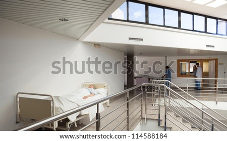 Patient lying in bed in hospital corridor