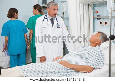 Patient lying in bed in hospital room talking to doctor