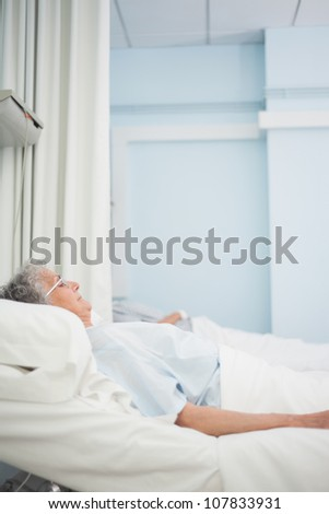 Patient lying on a medical bed in hospital ward