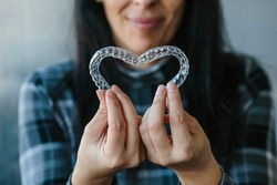 Patient making a heart shape with dental aligners
