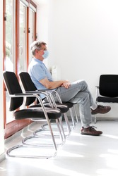 Patient or visitor with surgical mask sitting in a waiting room of a hospital or office - focus on the face