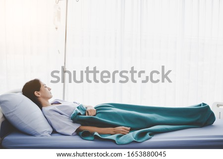 Patient person sleep on patient bed in hospital room. Sick woman get high fever. Illness girl get Surveillance or quarantine symptoms in separate patient room. She get tired, weak. Patient get cancer
