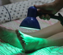Patient receiving color therapy, chromotherapy on body treatment with green light. Colorful lights stimulating the psyche.