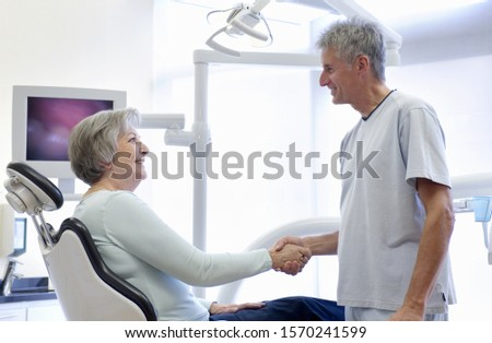 Patient sitting in dentist's chair shaking hands with dentist