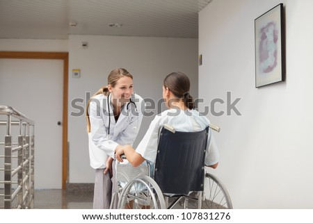 Patient sitting on a wheelchair in front of a doctor in hospital hallway